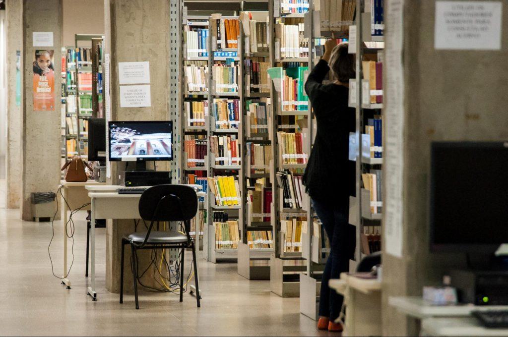 Interior de biblioteca com estantes de livros enfileiradas e um computador