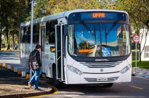 Ônibus branco estacionado enquanto estudantes entram no veículo