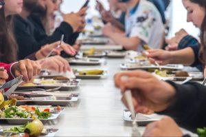 Mesa coletiva com várias pessoas almoçando em bandejas de alumínio