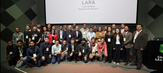 Grupo de pessoas em frente a um telão que diz Latin America Research Awards 2017 e mostra a logomarca do evento