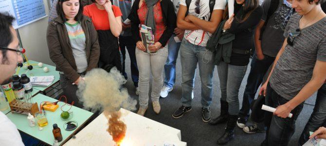 Grupo de estudantes em meia lua observam explosão gerada por experimento químico