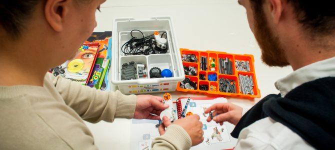 Peças de Lego e robótica sobre a mesa, manual de montagem aberto e dois estudantes de costas explorando o material.